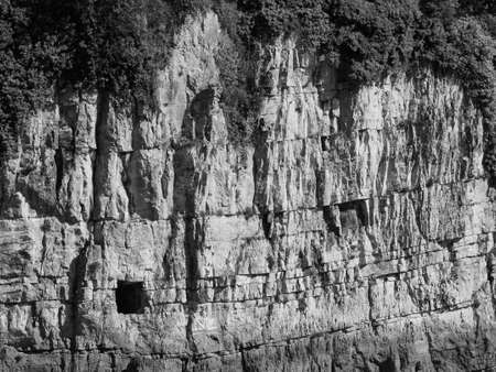 Gloucester Hole in the limestone cliffs of the River Wye in Chepstow, UK in black and white