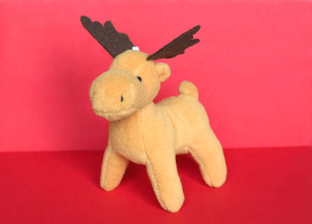 plush reindeer stuffed toy animal over red background