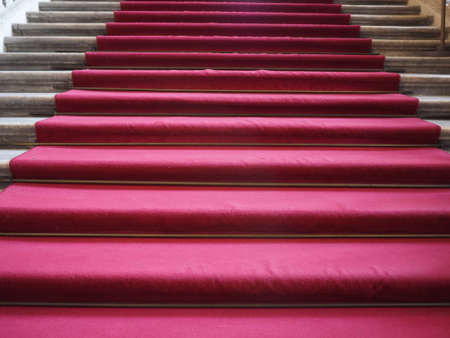 Red carpet on a stairway used to mark the route on ceremonial and formal occasions or events Фото со стока