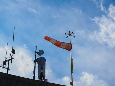 windsock and aerials over blue sky with clouds