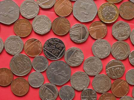 Pound coins money (GBP), currency of United Kingdom, over red background Archivio Fotografico