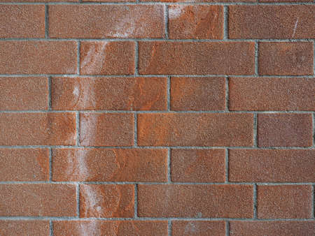 damage caused by efflorescence on a red brick wall