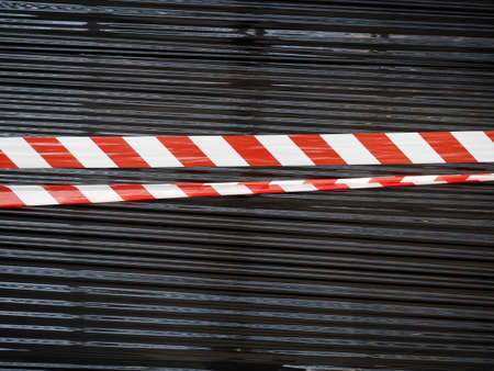 red and white barrier tape over black nylon background Stock Photo