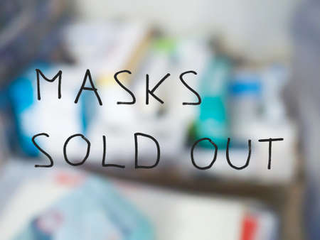 masks sold out sign on pharmacy shop window, with out of focus background of medicines and drugs Stock Photo