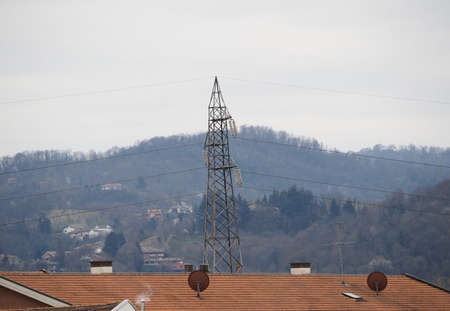 an electric power high voltage transmission line tower and satellite aerials on roof top