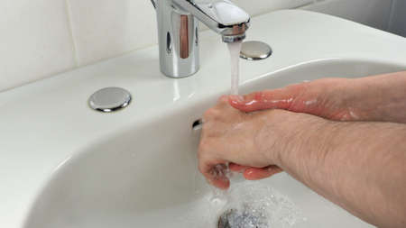 Unrecognisable man carefully washing hands at home for health safety