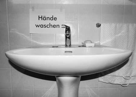 Haende waschen (translation: wash your hands) sign near bathroom basin