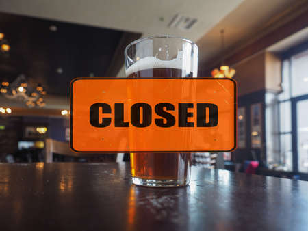 Empty pub, closed sign, pint of ale Stock Photo