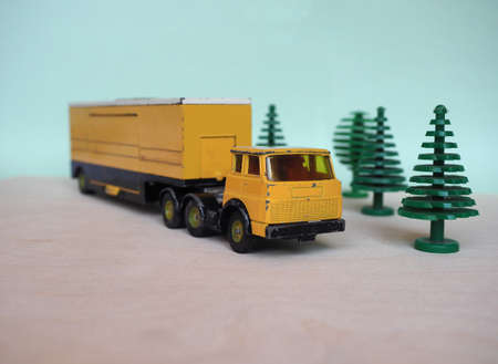 Vintage scale model yellow lorry with selective focus. Articulated vehicle with tractor and trailer. Stock Photo