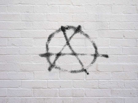 Circle A symbol of anarchy and anarchism spray painted on white brick wall