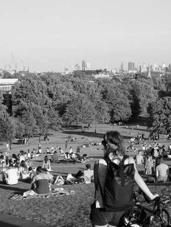 LONDON, UK - CIRCA SEPTEMBER 2019: People at Primrose Hill north of Regent's Park looking at London skyline at sunset in black and white