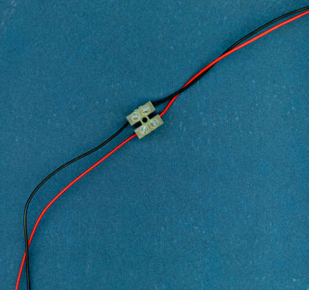 red and black electrical wires joined with paired screw terminal
