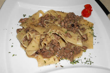 Tuscan tradition, tagliatelle with wild boar sauce in white plate photo