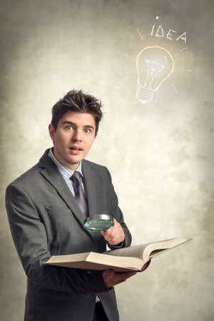 investigated: Young businessman looking at a book with magnifying glass Stock Photo