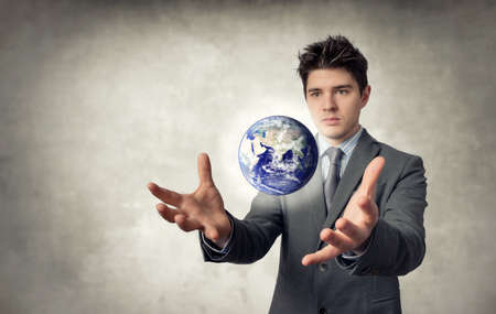businessman carrying a globe: Young businessman with planet That floats out of the hands