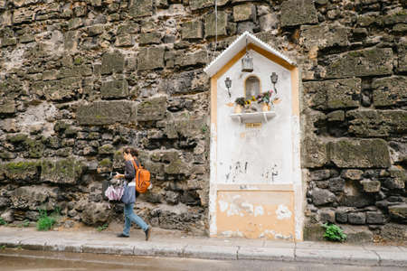 conceived: Palermo, Italy - May 12, 2016: woman walks in front of the wall. Votive shrine to the Virgin Mary Editorial