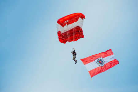 airpower: Zeltweg, Styria, Austria - September 3, 2016: Parachutist who hovers in the air with the Austrian flag on international event AIRPOWER16
