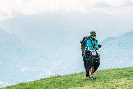 Monte Avena Feltre, Italy - July 5, 2017 : Pilot preparing to take off during 15th Fai Paragliding World Championship.