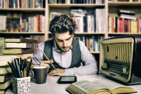 verdi: young adult reading an ebook over a desk full of books and various objects Stock Photo