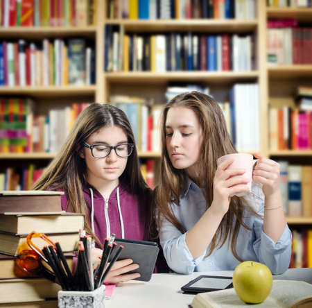 Young students reading an ebook over a desk full of various objects Stock Photo
