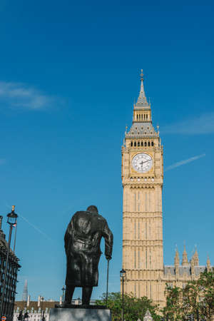A close-up shot of the Sir Winston Churchill statue in Westminster, London. The Big Ben in the background.
