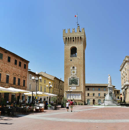 Recanati, Italy - August 21st, 2018: Piazza Giacomo Leopardi. Civic tower with clock and tourists strolling Editorial