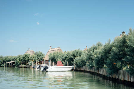 Caorle, Venice lagoon Italy. Boats moored in front of the characteristic casoni. The casone is a rural building with a rectangular plan, with a pitched roof covered with straw, masonry walls or branches and straw.