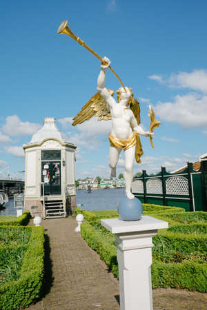 Zaanse Schans, Netherlands - May 14, 2019: white and golden wooden statues of an angel playing the trumpet Editorial