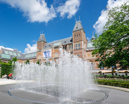 Amsterdam, Netherlands - May 13, 2019: Garden fountain and in the background the Rijksmuseum in Amsterdam
