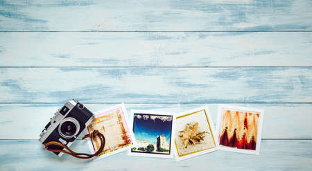 Photographic prints and camera on colored wooden panel
