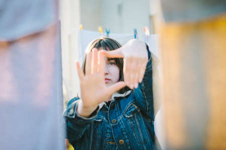 Portrait of cute girl outdoors with frame hands in front of face Zdjęcie Seryjne