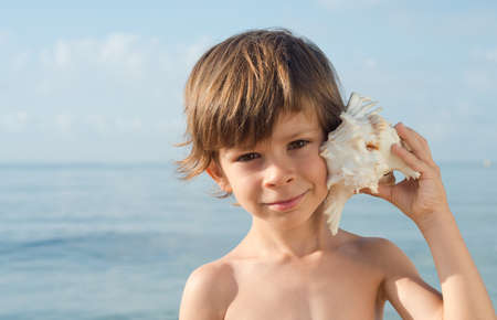 without clothes: child hears at sea conch Stock Photo