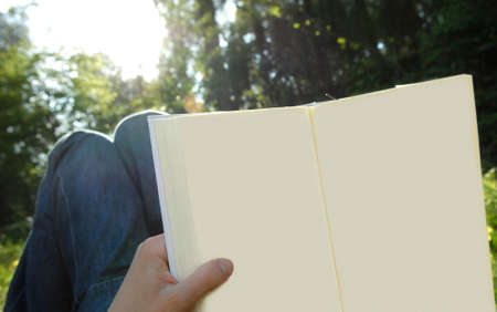 without: lying on the field reading an open book without text