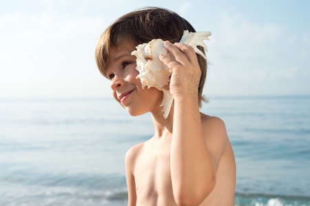 without clothes: child listening conch looking sideways at the beach foreground