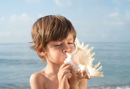 without clothes: child blowing conch looking up at sea Stock Photo