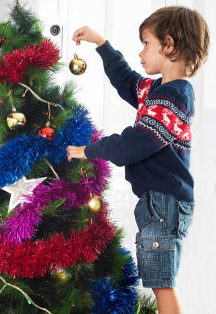 decorating christmas tree: Boy decorating Christmas tree Stock Photo