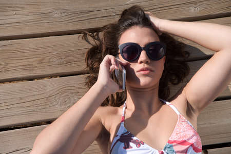 preoccupation: young woman stretched listening to telephone with bikini the sun Stock Photo