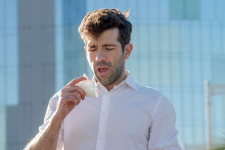 constipated: Young man with handkerchief about to sneeze Stock Photo