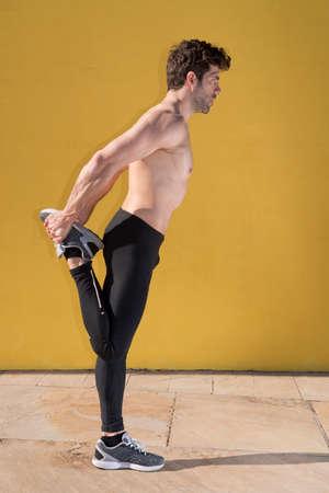 sportsmen: sportsmen stretching warming leg Stock Photo