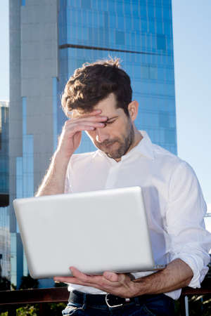 fear of failure: Man with laptop outdoors have problems Stock Photo
