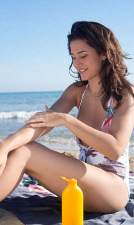 young woman on the beach applying sunscreen