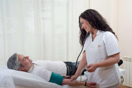 paciente en camilla: médico toma la presión arterial al paciente tendido en la camilla