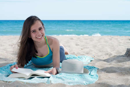 cheerfull: happy girl on the beach with book Stock Photo