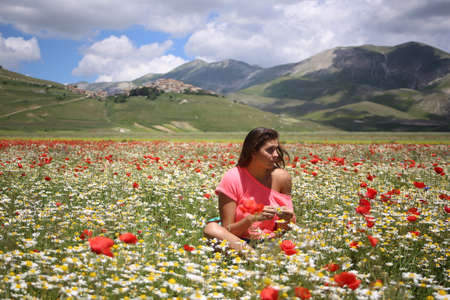 young woman sitting among the flowers  photo