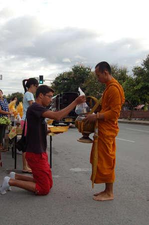 limosna: ourists y lugareños dan comida limosna a los monjes durante la mañana