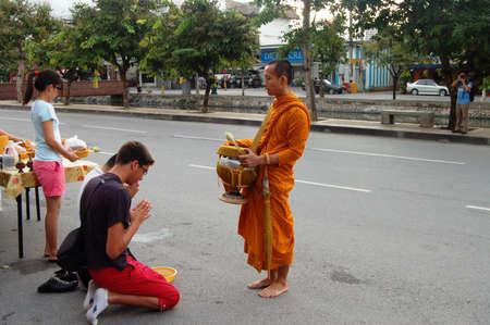 limosna: ourists and locals give alms food to monks during the morning