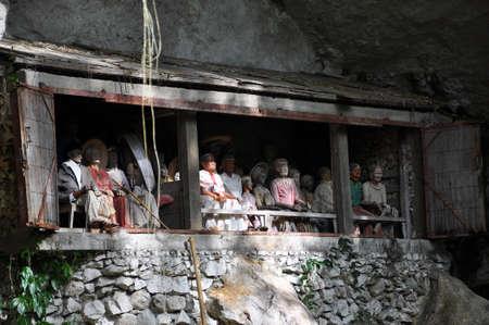 toraja: Groups of old family coffins with bones hanging on a rock. Tana Toraja region. Sulawesi island. Indonesia Editorial