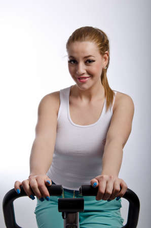 Young woman exercising on a bicylce shot in the studio photo