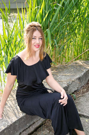 fine cane: Beautiful girl siting near a lake and enjoying the sun