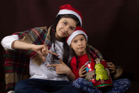 two girls posing with christmas hats and a gift